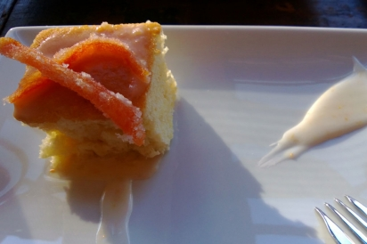 Essence of grapefruit cake topped with candied grapefruit and grapefruit glaze swoosh